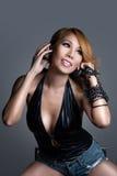 演奏音乐的年轻性感的亚裔妇女dj 库存图片