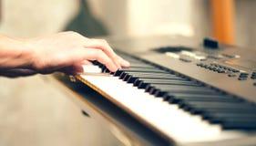 演奏音乐键盘的人手户内 免版税库存图片