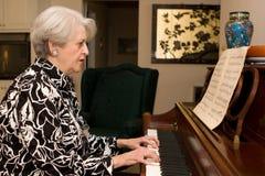 演奏高级妇女的钢琴 库存照片