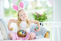 演奏鸡蛋的逗人喜爱的小女孩佩带的兔宝宝耳朵在复活节寻找 免版税库存图片