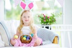 演奏鸡蛋的逗人喜爱的小女孩佩带的兔宝宝耳朵在复活节寻找 免版税库存照片