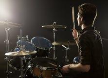 演奏鼓成套工具的鼓手背面图在演播室 库存图片