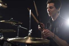 演奏鼓成套工具的年轻鼓手侧视图在演播室 库存照片
