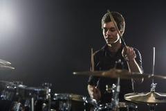 演奏鼓成套工具的年轻鼓手在演播室 库存照片