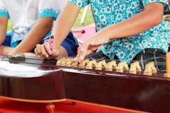 演奏洋琴泰国的孩子 免版税库存图片