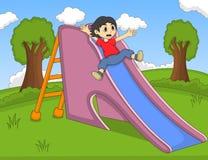演奏幻灯片的孩子在公园动画片 库存图片