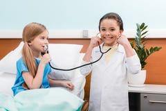 演奏医生和患者有听诊器的小女孩在医院 免版税库存图片