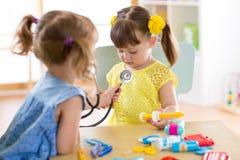 演奏医生和医院的两个逗人喜爱的孩子使用听诊器 有朋友的女孩乐趣在家或幼儿园 库存图片