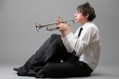 弹他的喇叭的一个年轻人的画象 免版税库存照片