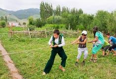 演奏绳索的猛拉孩子在中亚村庄  免版税库存照片