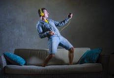 演奏Air Guitar的可爱和凉快的愉快的人听到与拿着手机的黄色耳机的音乐跳在顶部 库存图片