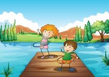 演奏hulahoop的两个孩子在河 免版税库存图片