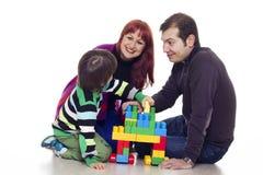 演奏lego的父亲、母亲和儿子 免版税库存图片