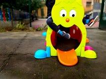 演奏otudoor的小孩在有一个五颜六色的玩具、乐趣和戏剧概念的一个操场 免版税库存图片