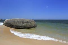 演奏parasail的游人在岩石海滩 图库摄影