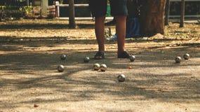演奏Petanque在公园-金属球和橙色木球在岩石围场有站立一个的人的在阳光下 免版税库存照片