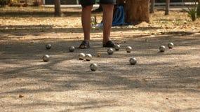 演奏Petanque在公园-金属球和橙色木球在岩石围场有站立一个的人的在阳光下 免版税库存图片