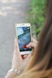 演奏Pokemon的女孩在她的智能手机去 免版税库存照片