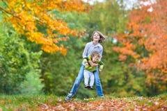 演奏togeter的两个孩子在秋天公园 免版税库存照片