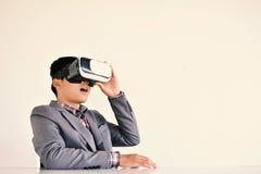 演奏VR虚拟现实玻璃箱子的亚洲商人 免版税图库摄影