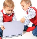 演奏woth膝上型计算机的双胞胎 库存图片