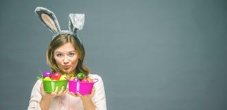 演播室射击了一个愉快的少妇佩带的兔宝宝耳朵和阻止在她的眼睛前面的一个五颜六色的复活节彩蛋 免版税图库摄影