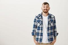 演播室射击了与胡子和时髦的短的理发的正面快乐的白种人男性模型,握在口袋的手和 库存照片
