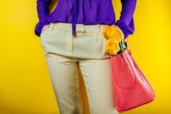 演播室射击了妇女佩带的春天成套装备和拿着与黄色郁金香的一个袋子 图库摄影