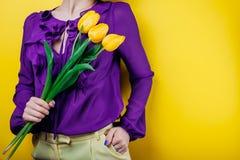 演播室射击了妇女佩带的春天成套装备和拿着黄色郁金香 库存照片