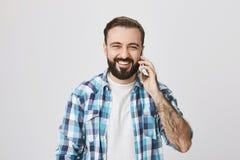 演播室射击了有时髦理发和胡子的成年男性欧洲人,高兴地微笑,当谈话在电话和看时 免版税库存图片
