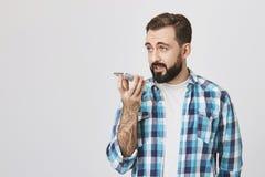 演播室射击了男性欧洲成人举行的电话在嘴附近,当谈话与它在报告人,站立反对灰色时 免版税库存照片