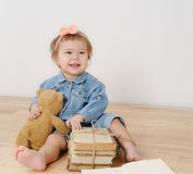 演播室射击了有他的玩具和书的小逗人喜爱的微笑的女孩 库存图片
