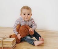 演播室射击了有他的玩具和书的小逗人喜爱的微笑的男孩 库存照片