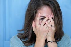 演播室射击了深色的女孩掩藏的眼睛在手下,当感到感到羞愧时 免版税图库摄影