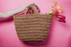 演播室拿着与郁金香的射击了妇女秸杆袋子在桃红色背景 春天销售在商店 赞誉 免版税库存照片