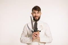 演播室拿着在白色背景的射击了一位愉快的有胡子的年轻厨师快刀 有刀子的主厨 英俊的微笑的cheef举行 库存图片