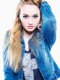 演播室显示信心的射击了一个年轻和有吸引力的女性模型穿一件灰色T恤杉和牛仔布夹克 在空白背景 库存照片