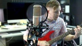 演播室的人创造性的音乐家工作在弹,唱和记录有室内笔记本和话筒的吉他旁边 股票视频