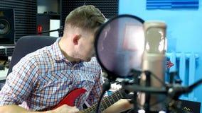 演播室的人创造性的音乐家工作在弹,唱和记录有室内笔记本和话筒的吉他旁边 股票录像