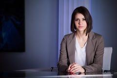 演播室的年轻美丽的深色的电视主持人在活广播期间 编辑的女性电视主任在演播室 免版税库存照片
