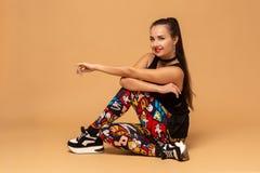 演播室背景的年轻女性舞蹈家 年轻现代样式舞蹈家女孩坐地板在演播室 图库摄影