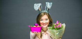 演播室被射击一个愉快的年轻女人佩带的兔宝宝耳朵和阻止一个五颜六色的复活节彩蛋 免版税图库摄影