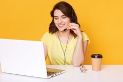 演播室被射击耳机的微笑的快乐的支持电话操作员妇女有与她的客户的交谈,隔绝在黄色 免版税库存图片