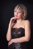 演播室黑暗背景的可爱的白肤金发的妇女 图库摄影