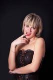 演播室黑暗背景的可爱的白肤金发的妇女 免版税库存图片