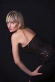演播室黑暗背景的可爱的白肤金发的妇女 库存照片