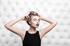 演播室画象一性感白肤金发在黑礼服 库存图片