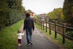 漫步在小径的年轻爸爸和小孩女孩 免版税库存照片