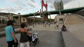 漫步在巨大的蜘蛛雕塑,夏天晚上附近的许多游人在毕尔巴鄂 影视素材