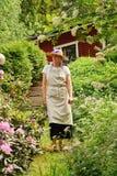 漫步在庭院里的资深妇女 免版税库存图片